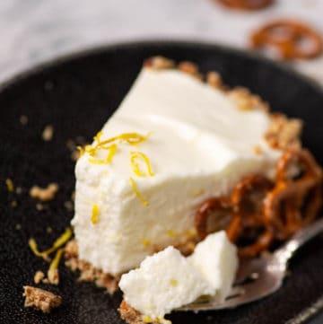A slice of Lemon Chiffon Pie with a bite on a fork