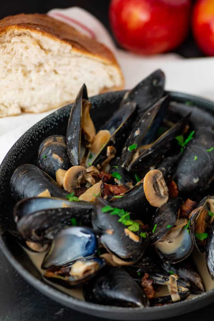 A bowl of Mussels with Apples with a slice of bread