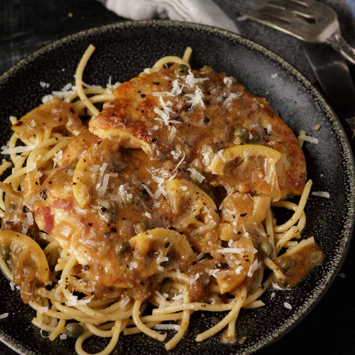 A plate of pasta with chicken piccata on top