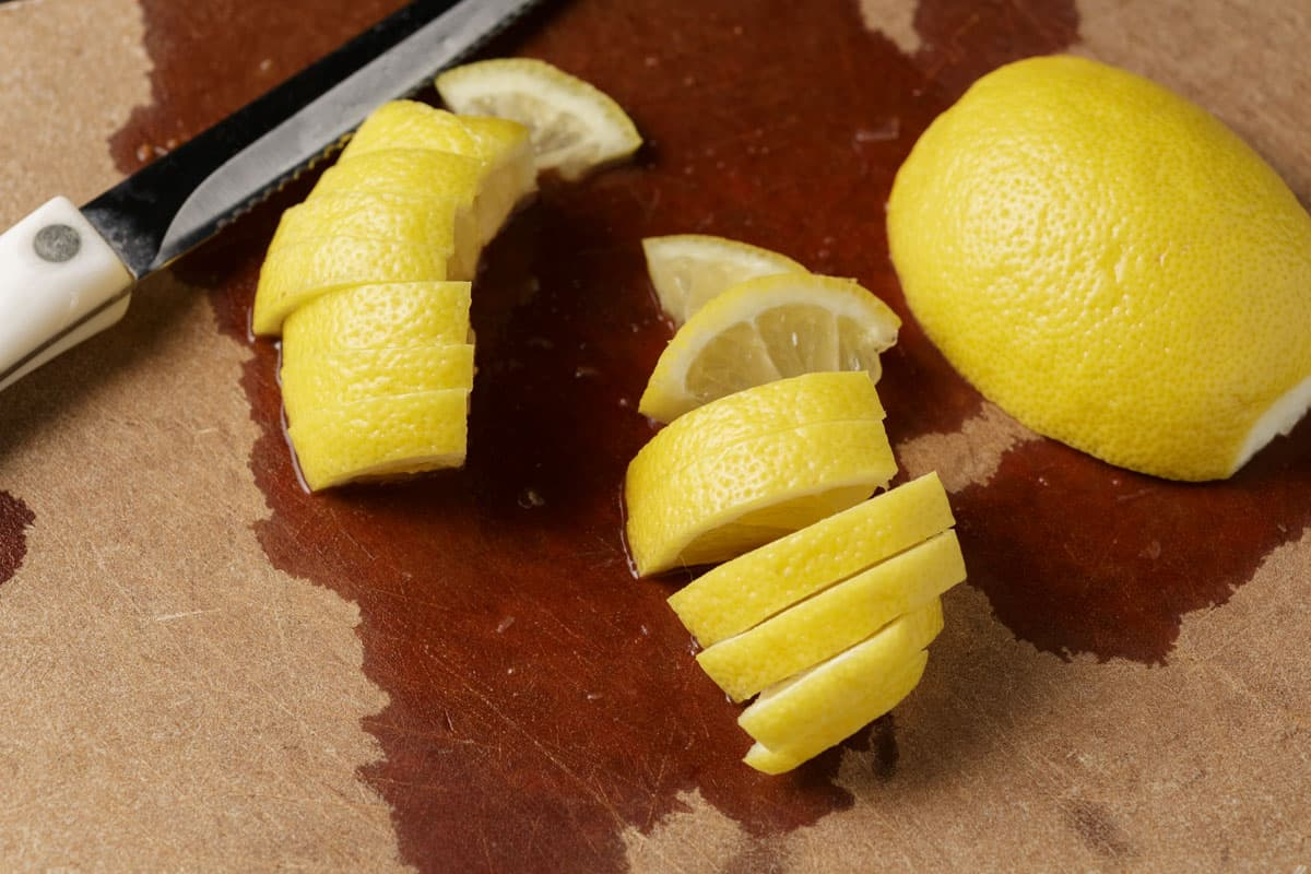 A lemon being sliced into thin slices on a cutting board