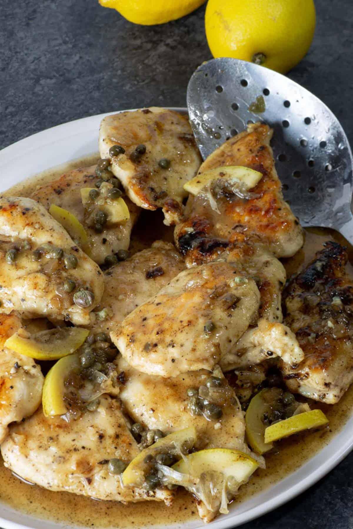 A white platter of chicken piccata