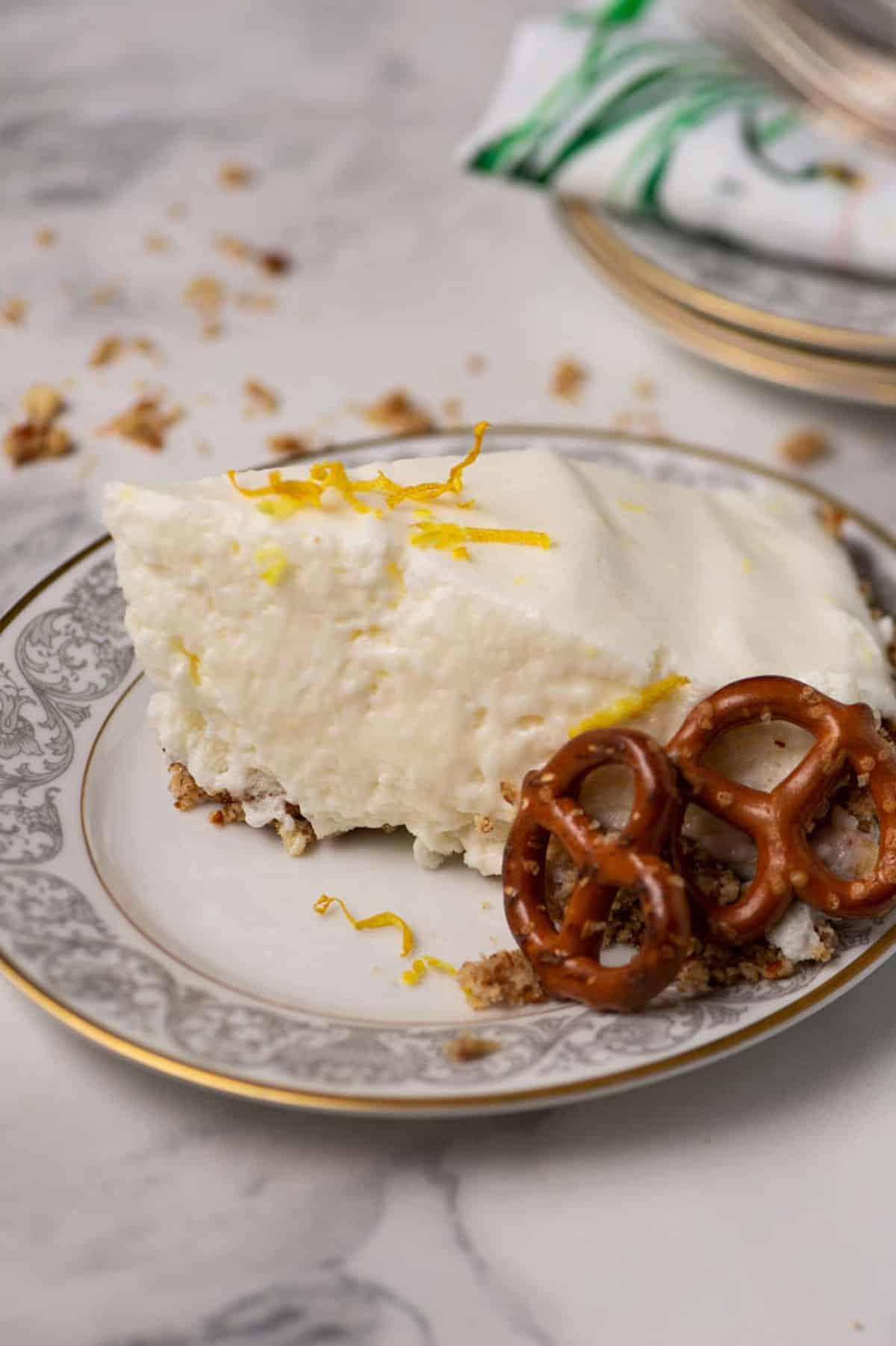 A slice of lemon chiffon pie with pretzels on a china plate.