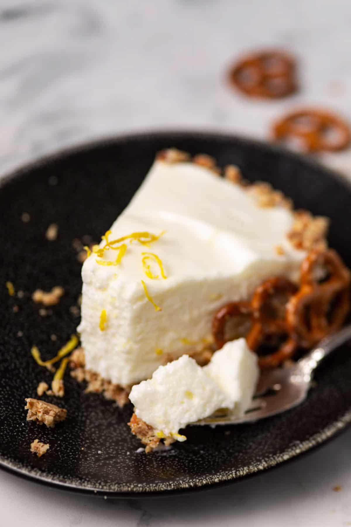 A bite of a lemon chiffon pie on a black plate.