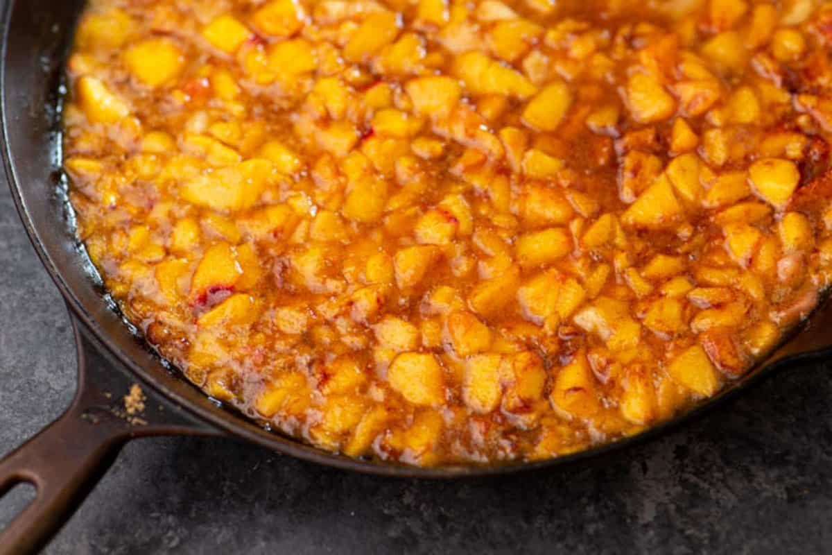 An iron skillet with chopped peaches.