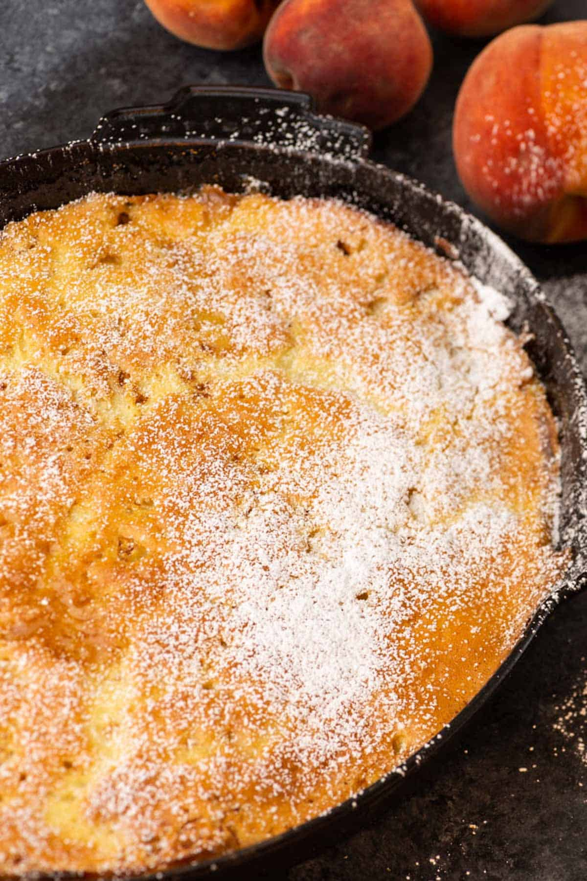 A baked peach pancake with powdered sugar on top.