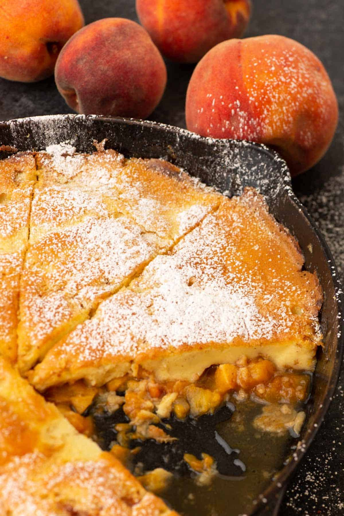 A baked peach Dutch baby pancaked in an iron skillet.