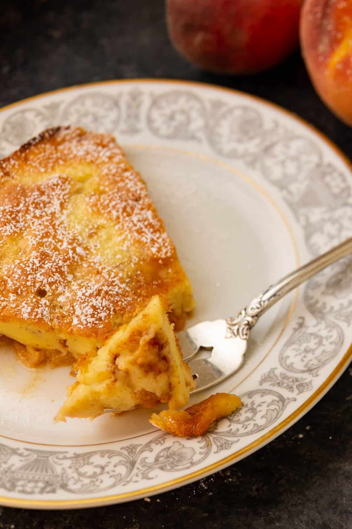 A fork full of a Dutch baby pancake on a plate.