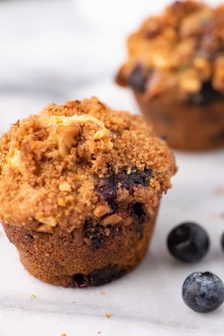 A Blueberry Muffin with Streusel Topping on a marble board