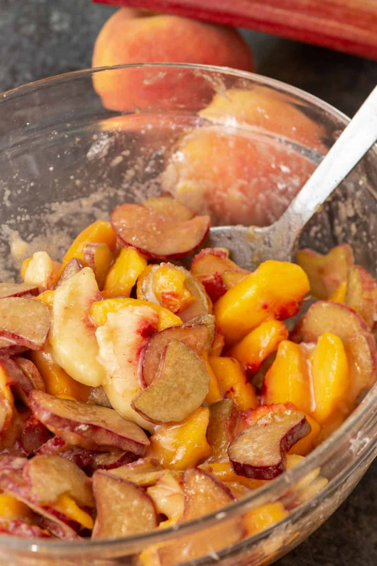 A bowl of peaches and rhubarb with sugar and cornstarch.