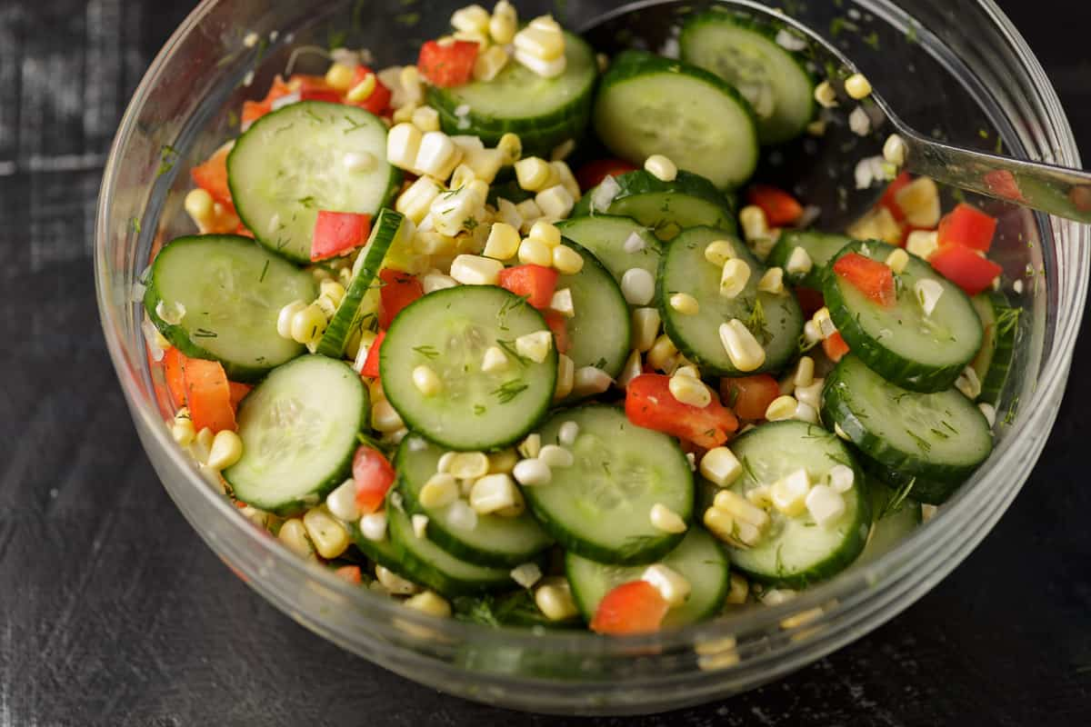 A bowl of cucumber salad with corn and red peppers in a glass bowl