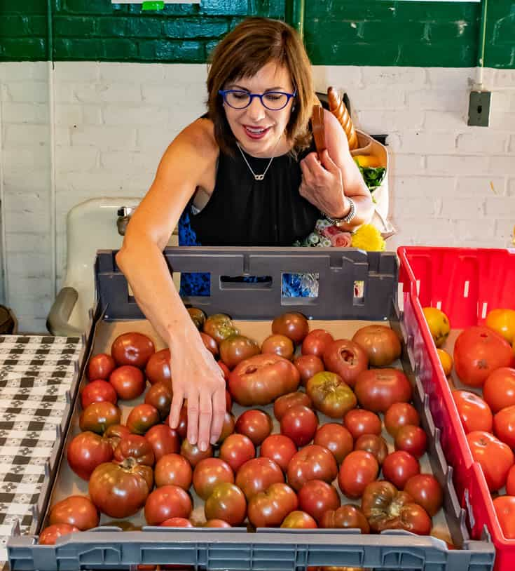 Barbara choosing a tomato at the farmers market