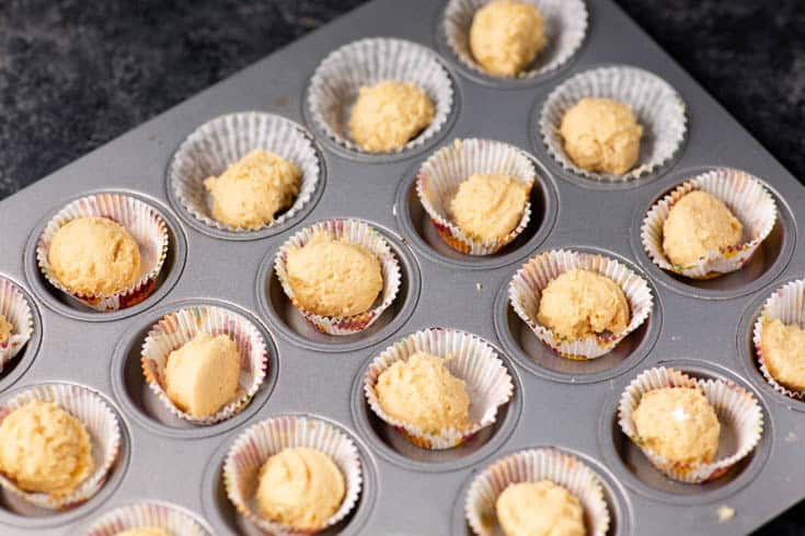 A mini muffin pan filled with cookie dough