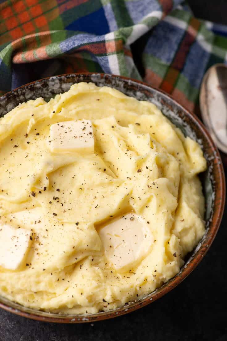 A bowl of make-ahead mashed potatoes with butter melting on top
