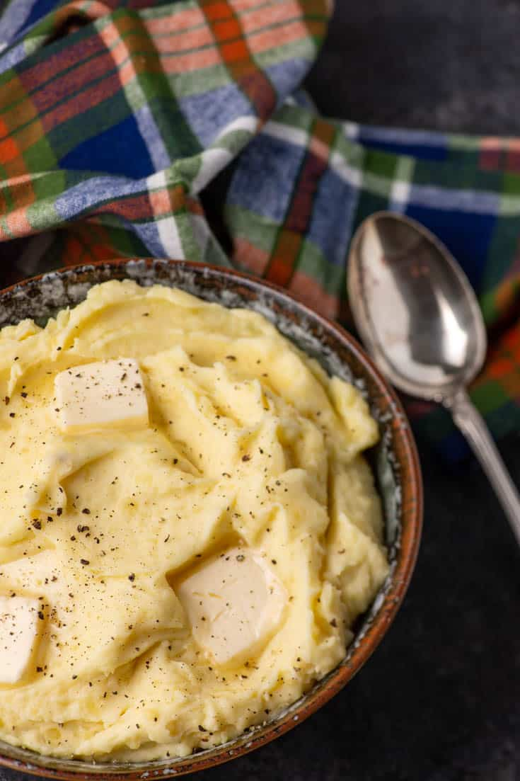A bowl of creamy mashed potatoes with a serving spoon