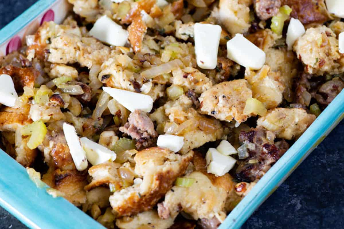 Homemade stuffing with butter chunks on top before baking.