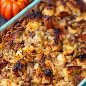 Baked stuffing in a casserole dish with pumpkins in the background.