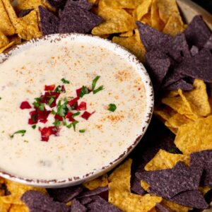 Corn chips surrounding a bowl of creamy queso dip.