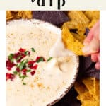 A hand dipping a chip in Queso Dip.