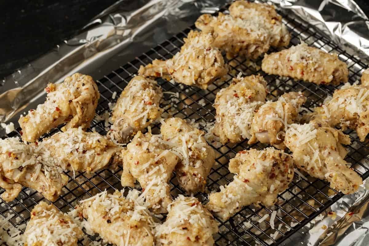 Chicken wings sprinkled with parmesan cheese on a baking rack.