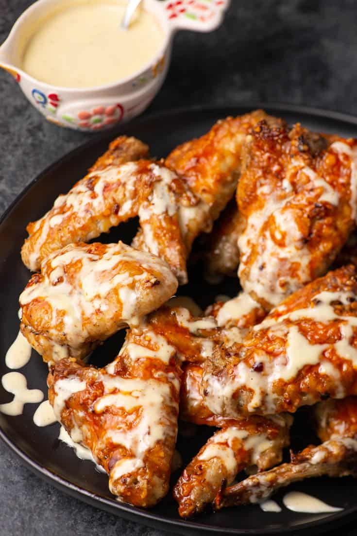 A platter of Buffalo Chicken Wings with Blue cheese dipping sauce drizzled over the top