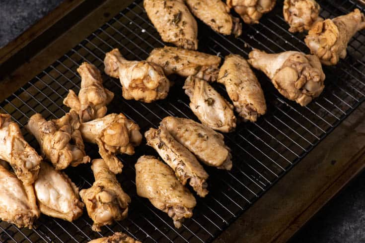 Boiled chicken wings drying on a rack before baking