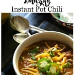 A bowl of instant pot chili with spoons, sour cream and cheddar cheese