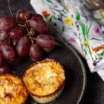 A black plate with two mini crustless quiches on them next to some red grapes
