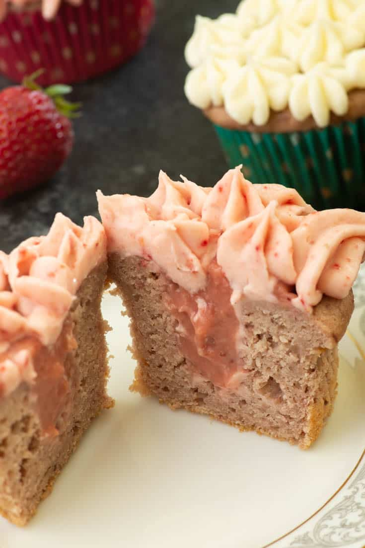 A strawberry cupcake cut in half with strawberry fillig