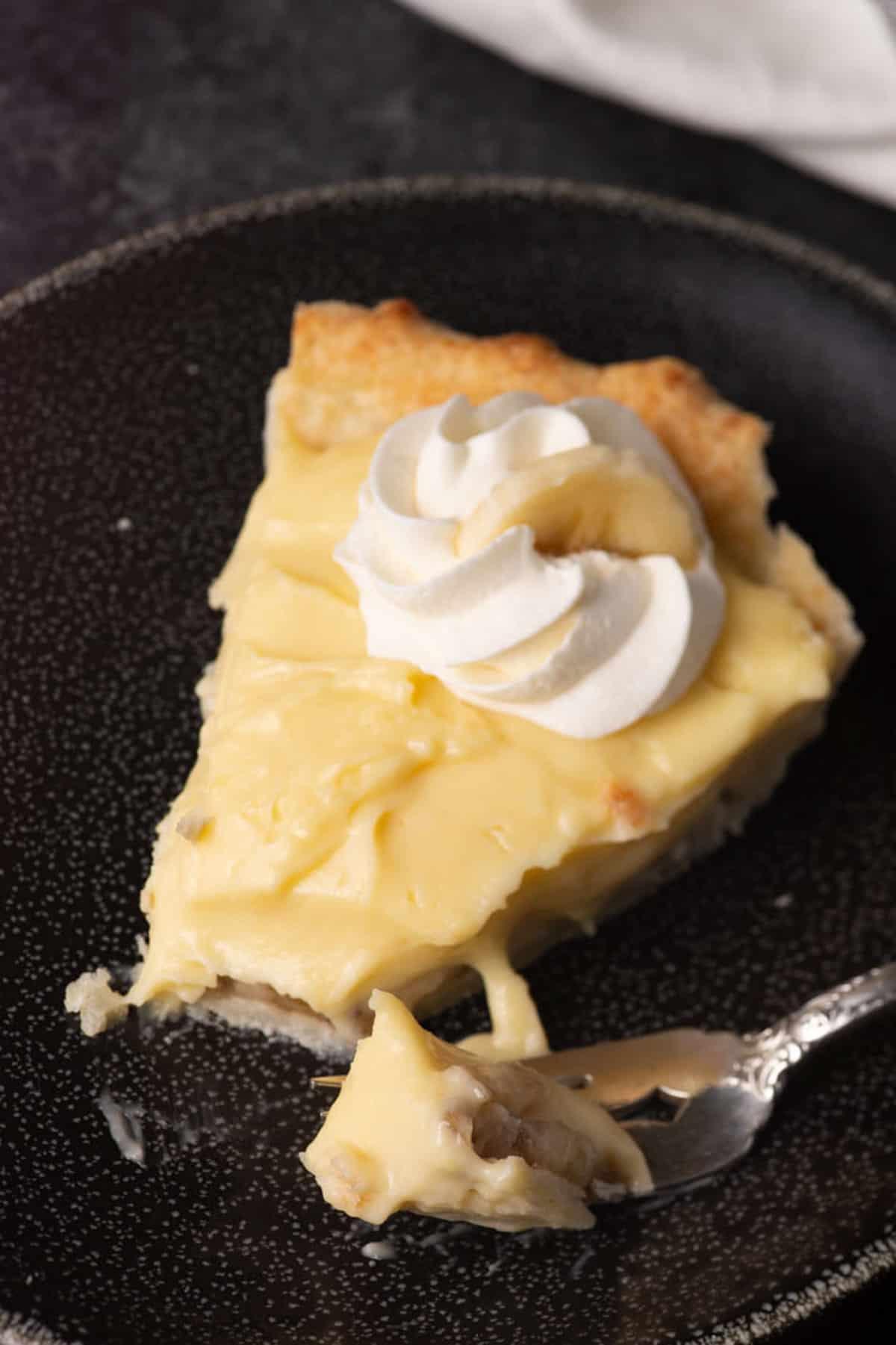 A bite of banana cream pie on a black plate.
