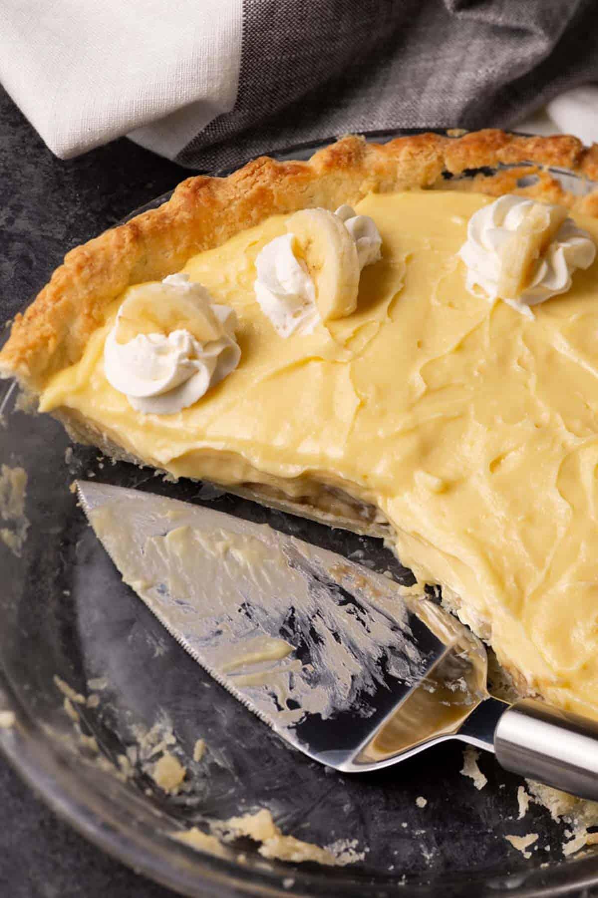 Part of. a banana cream pie with a pie server.