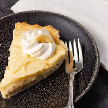 A slice of Banana cream pie on a black plate with a fork.