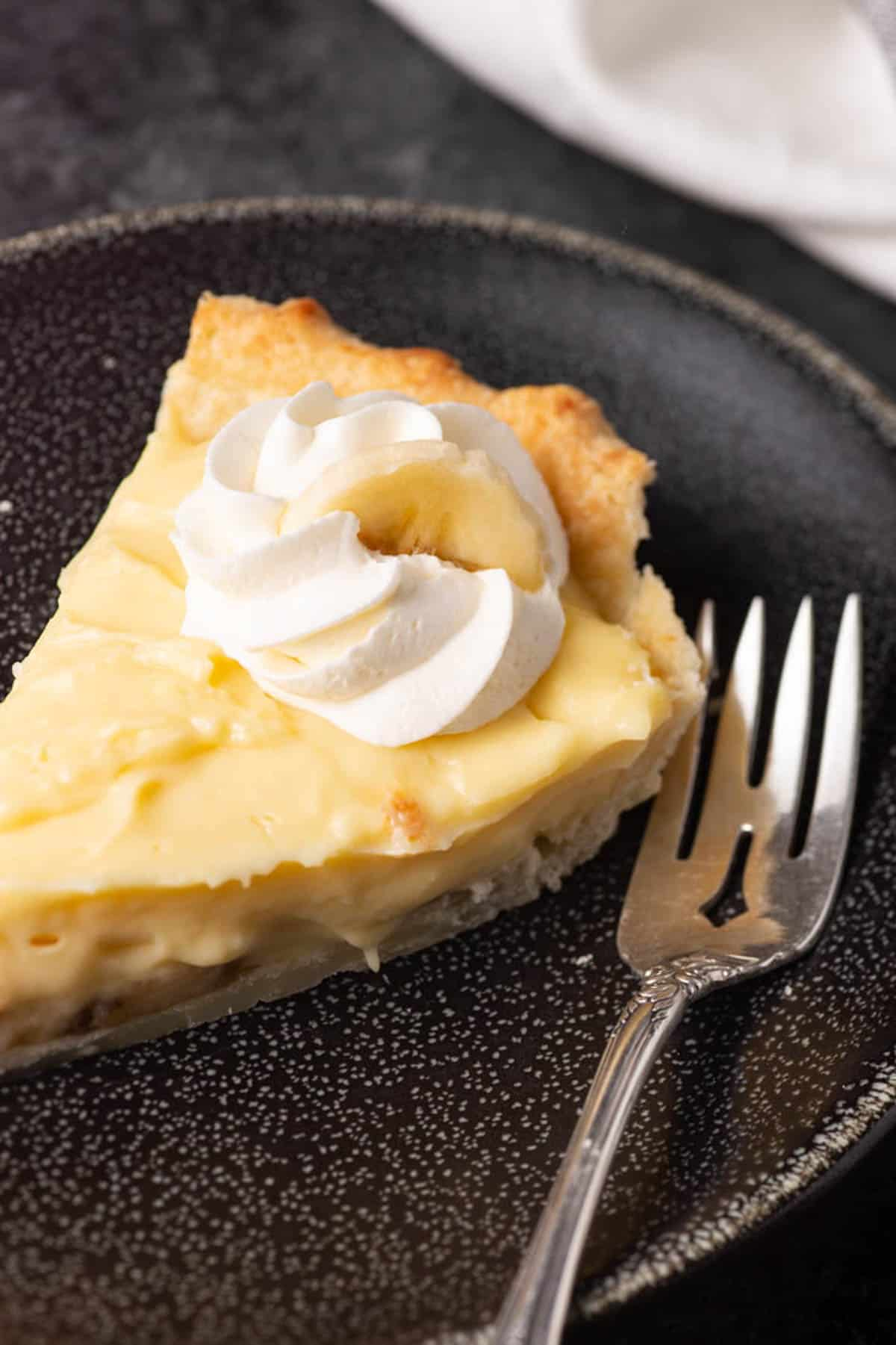 A slice of banana cream pie with whipped cream on top.