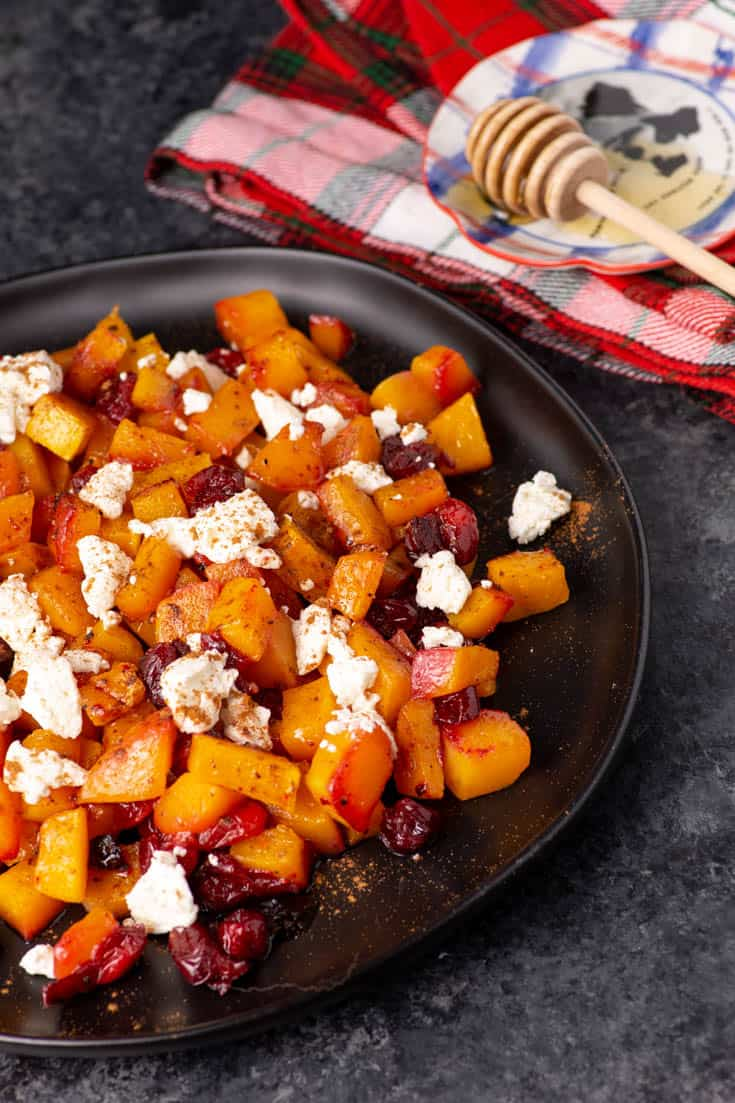 A black platter with roasted butternut squash with cranberries and feta