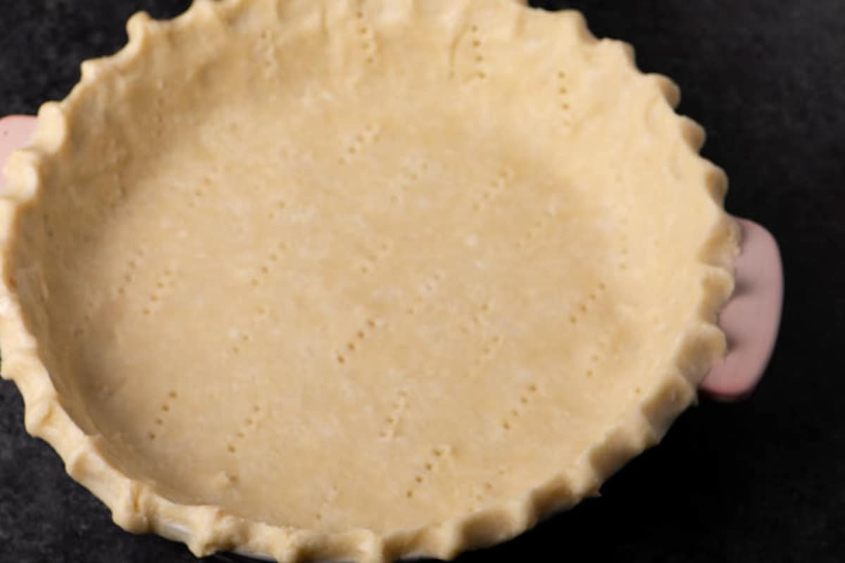 A pie crust with fluted edges in a pie pan.