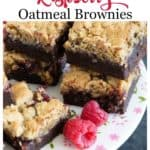 Stacks of raspberry oatmeal brownies on a cake platter with raspberries around it