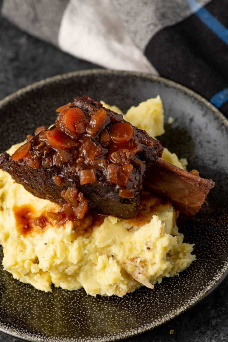 A plate of mashed potatoes with a beef short rib on top