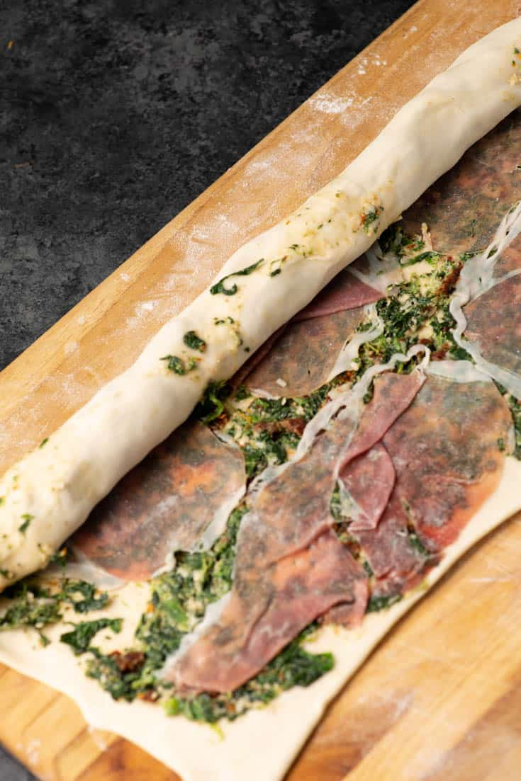 Preparing Puff pastry covered with spinach and prosciutto