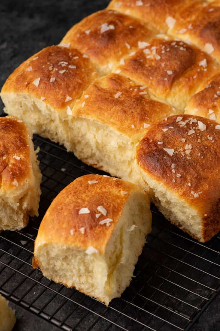 A batch of mashed potato rolls on a cooling rack