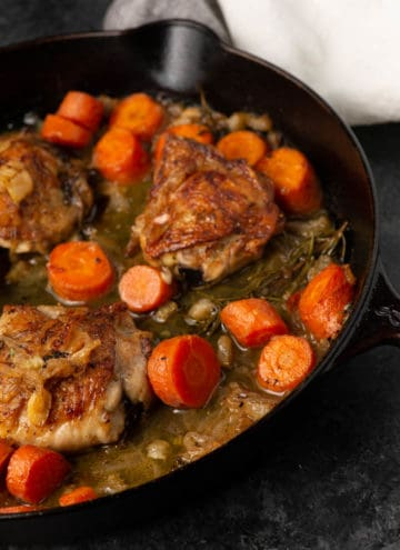 An iron skillet of chicken thighs cooked in wine with carrots