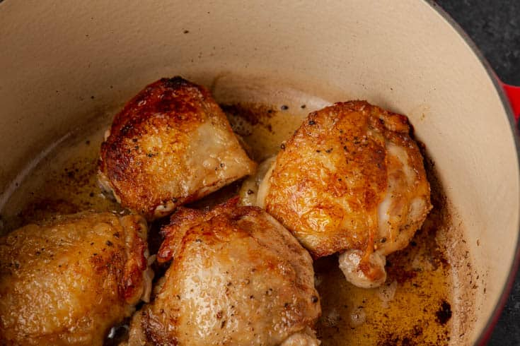 Browned chicken thighs in a Dutch oven