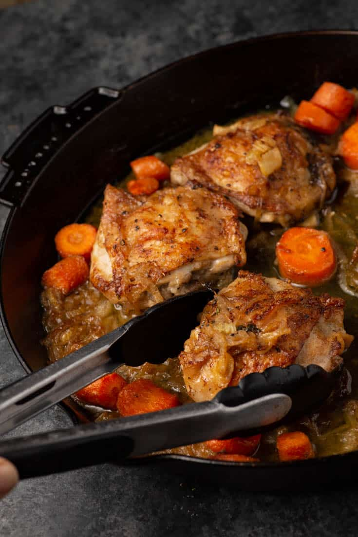 A browned chicken thigh being taken out of an iron skillet