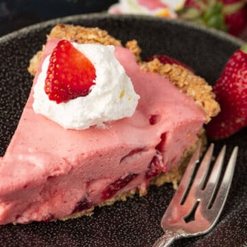 Strawberry chiffon pie with whipped cream and a strawberry on top.