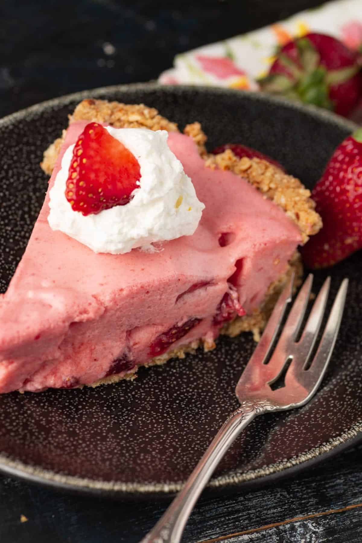 A slice of strawberry pie with a fork on the plate.