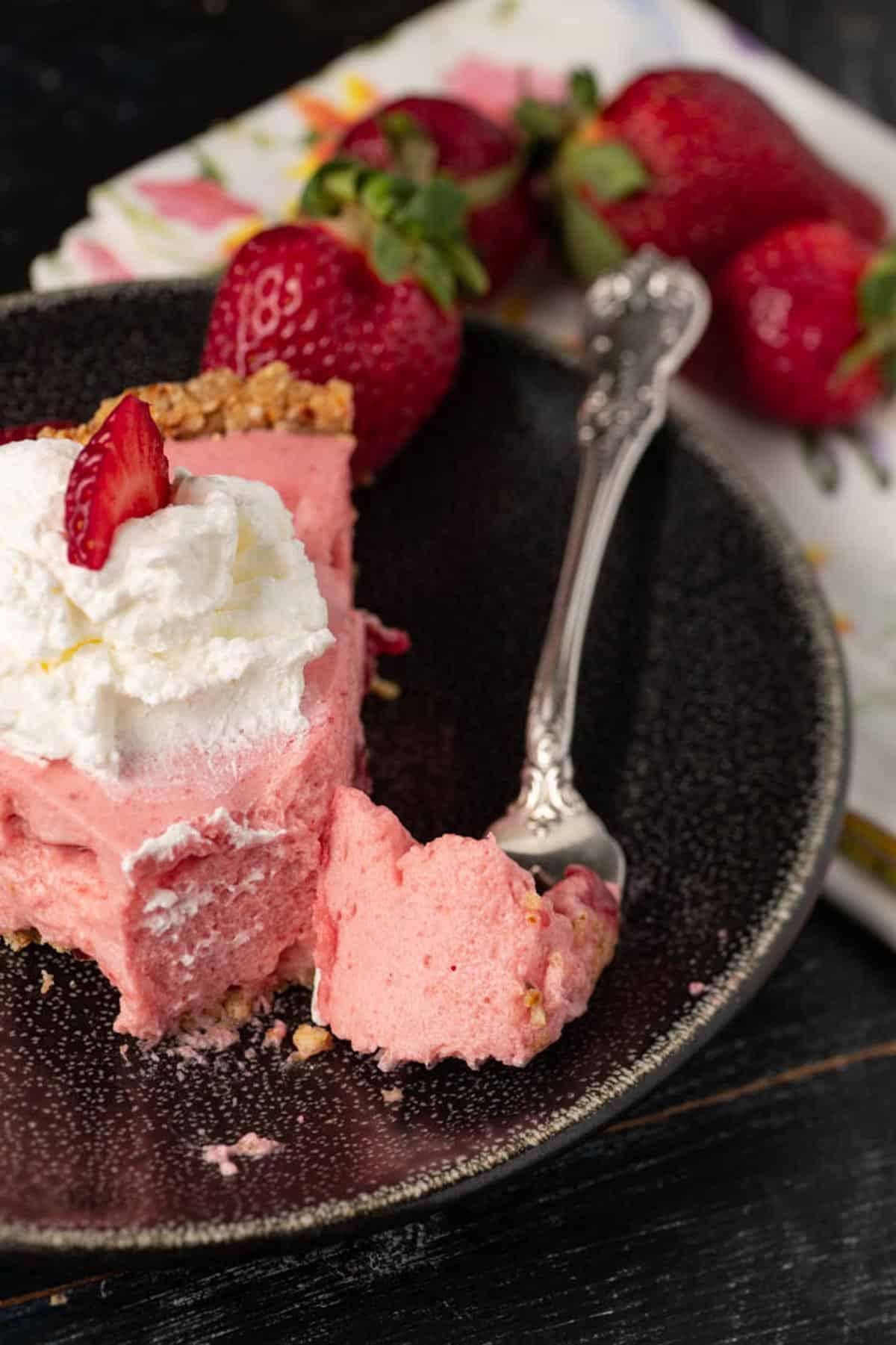 A bite on a fork of strawberry chiffon pie.