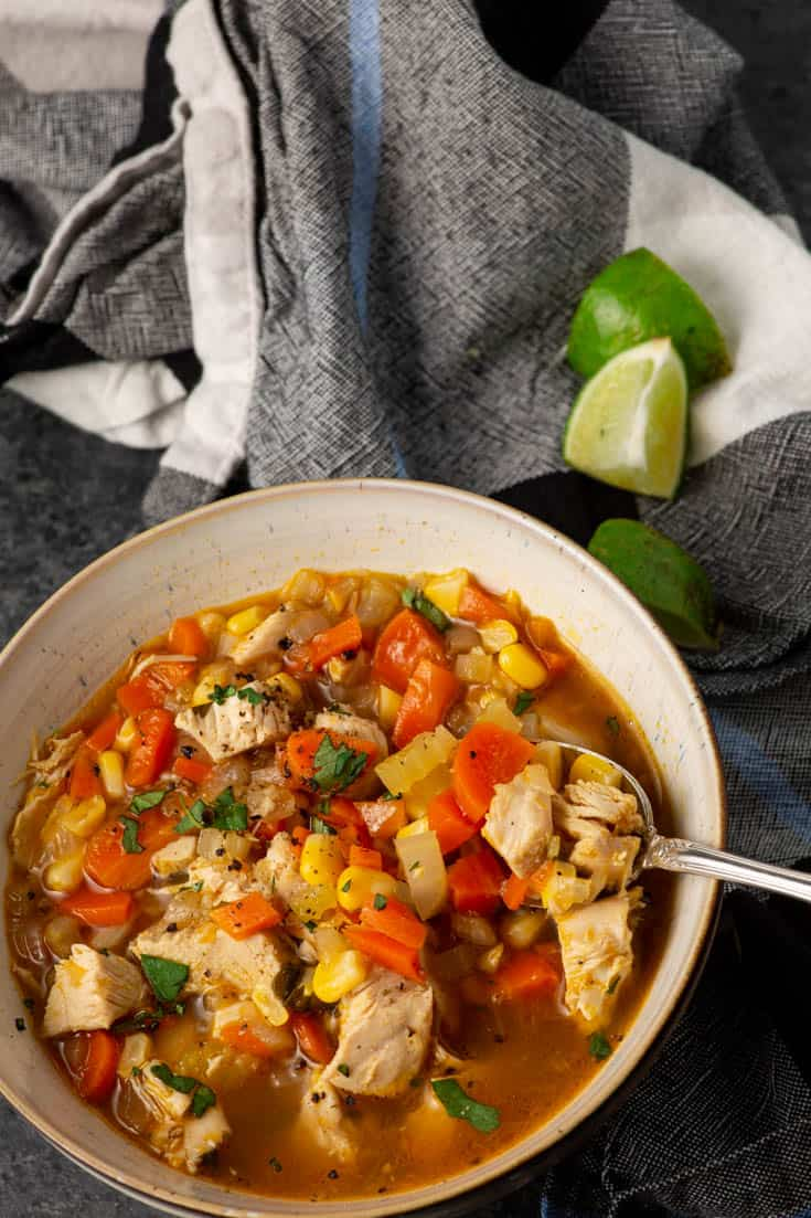 A bowl of chicken soup with limes