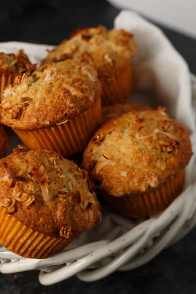 A white basket filled with banana granola muffins