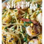 A platter of pasta with grilled corn and shrimp