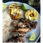 A platter of grilled chicken with pineapple and limes
