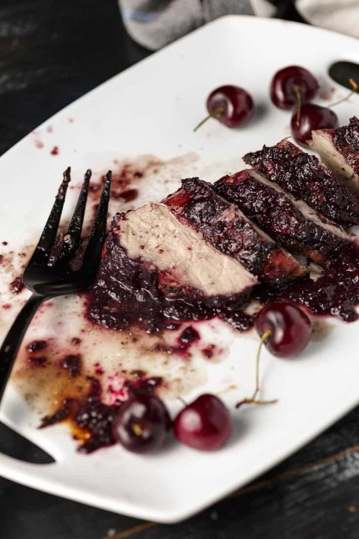 A fork on a platter with cherries and pork tenderrloin