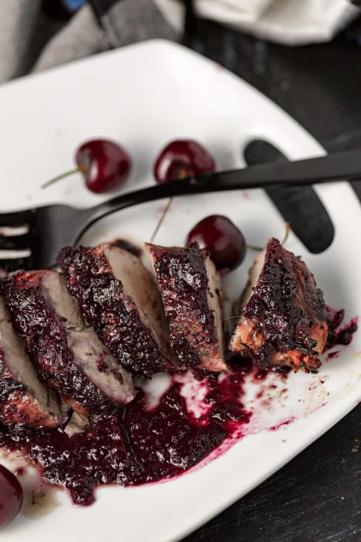 A platter of pork tenderloin covered with cherry sauce